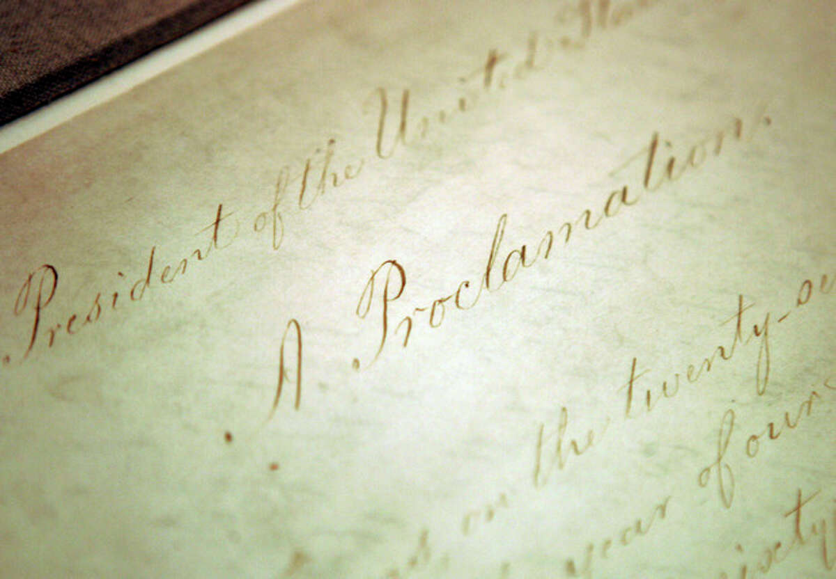 """FILE - This Feb. 18, 2005 file photo shows the original Emancipation Proclamation on display in the Rotunda of the National Archives in Washington. As New Year's Day approached 150 years ago, all eyes were on President Abraham Lincoln in expectation of what he warned 100 days earlier would be coming _ his final proclamation declaring all slaves in states rebelling against the Union to be """"forever free."""" A tradition began on Dec. 31, 1862, as many black churches held Watch Night services, awaiting word that Lincoln's Emancipation Proclamation would take effect as the country was in the midst of a bloody Civil War. Later, congregations listened as the president's historic words were read aloud. (AP Photo/Evan Vucci, File)"""