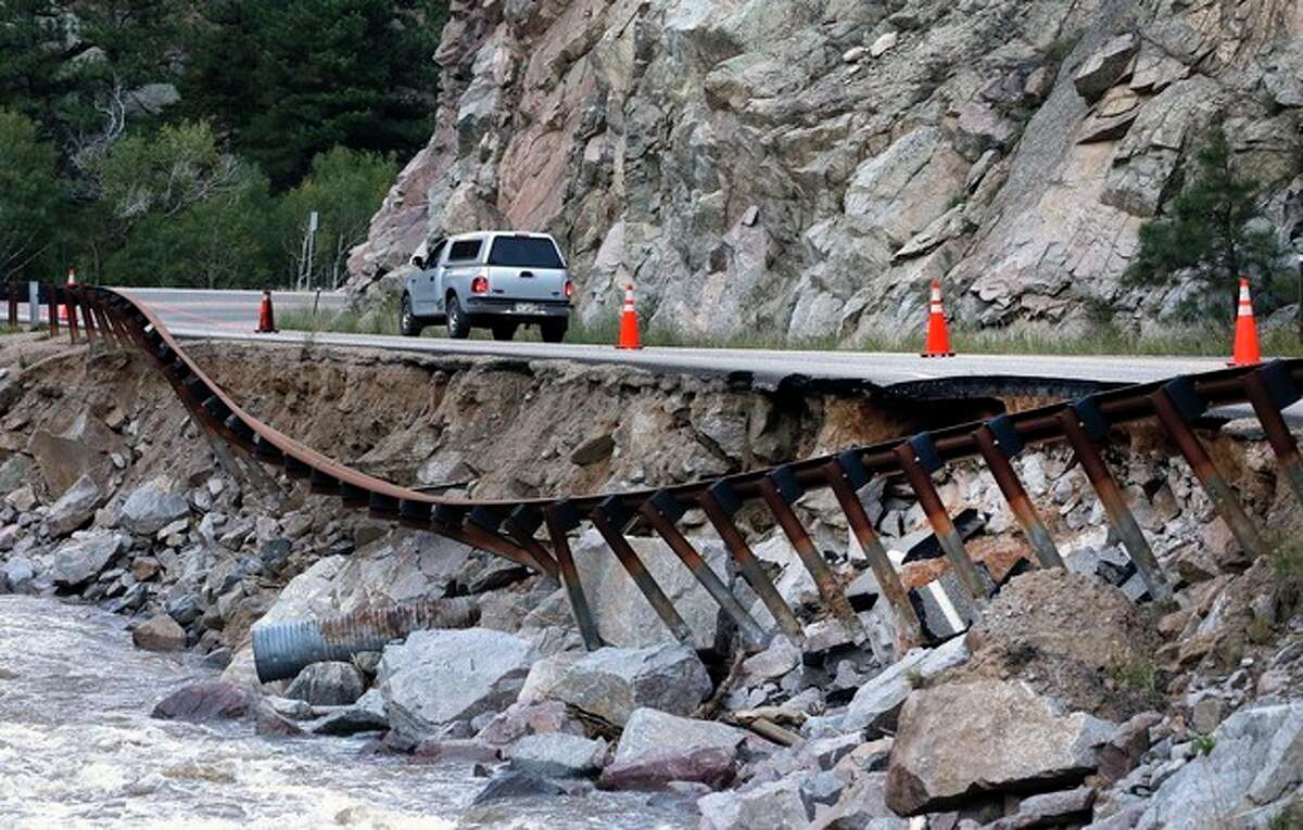 A guardrail hangs away from a closed canyon road, where some local residents are allowed to drive with caution, and which is washed out in places by recent flooding, up Boulder Canyon, west of Boulder, Colo., Friday Sept. 20, 2013. With snow already dusting Colorado?'s highest peaks, the state is scrambling to replace key mountain highways washed away by flooding. More than 200 miles of state highways and at least 50 bridges were damaged or destroyed, not counting many more county roads. (AP Photo/Brennan Linsley)