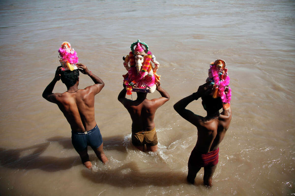 Indian devotees prepare to immerse idols of elephant-headed Hindu god Ganesha in the Chenab River during Ganesh Chaturthi festival celebrations in Akhnoor, India, Monday, Sept. 16, 2013. The festival is celebrated to mark the birth of Ganesha, the Hindu god of wisdom, prosperity and good fortune. (AP Photo/Channi Anand, File)