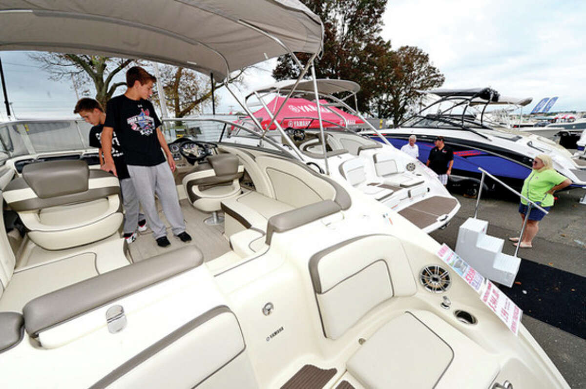 Hour photo / Erik Trautmann Visitors including Nicholas and Gene Schaeffer enjoy the Norwalk Boat Show Saturday at Cove Marina.