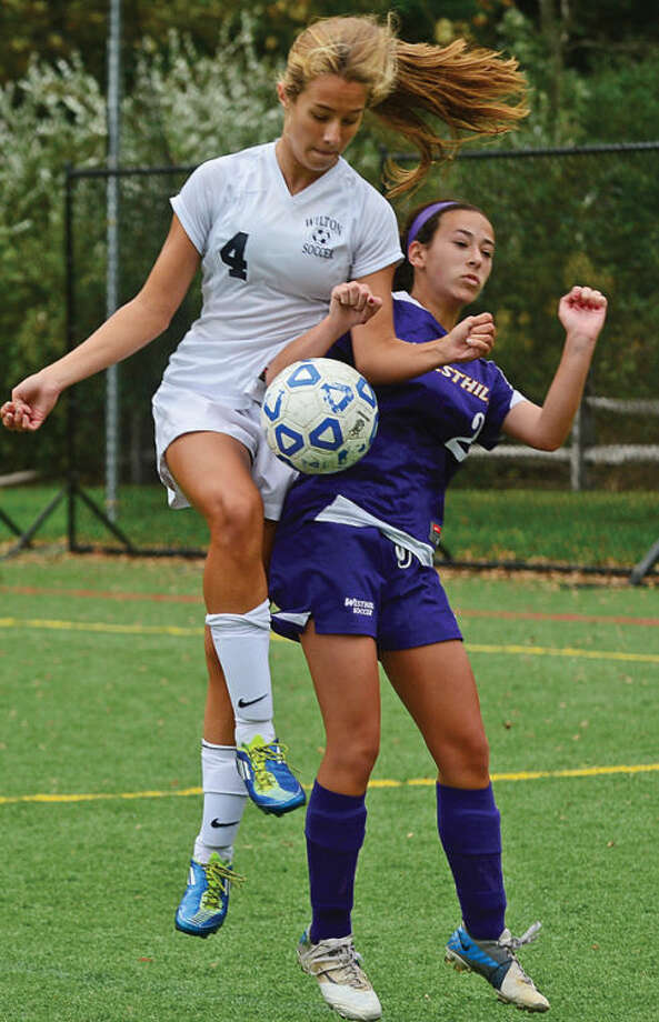 Wilton's # 4 Zoe Lamason battles against Westhill's #12 in their game Saturday.