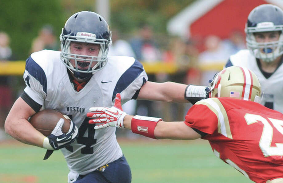 Hour photo/John NashWeston's Peter Lummis, left, stiff arms Stratford's Milo Mitchell while running the ball during Saturday's SWC game at Penders Field in Stratford. Lummis and the Trojans collected a 20-14 victory.