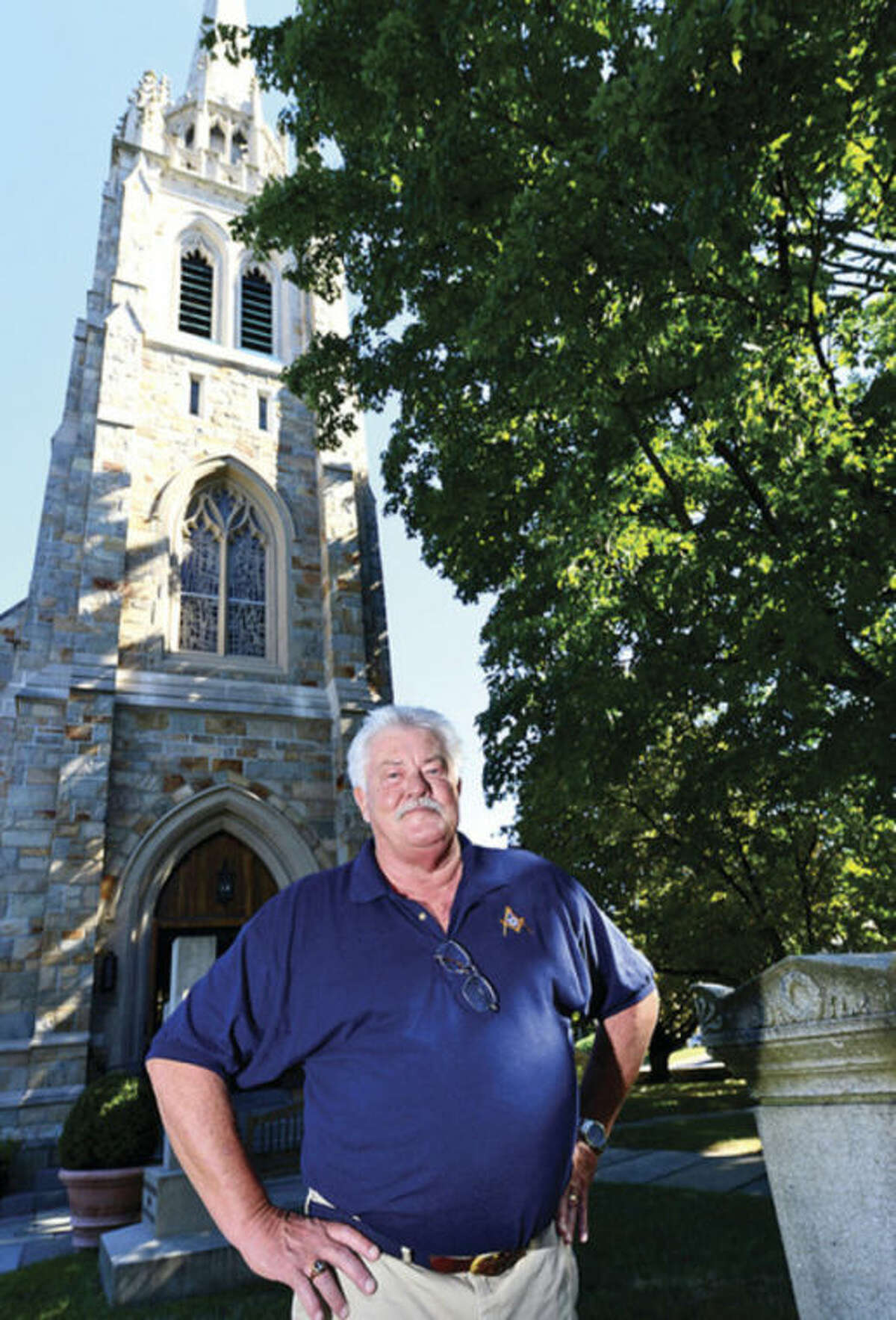 Hour photos / Erik Trautmann Ed Isaacs, at left, looks at some historical documents, and at right, stands in front of St. Paul's Church on the Green, for which his ancestors staked the ground in 1737.