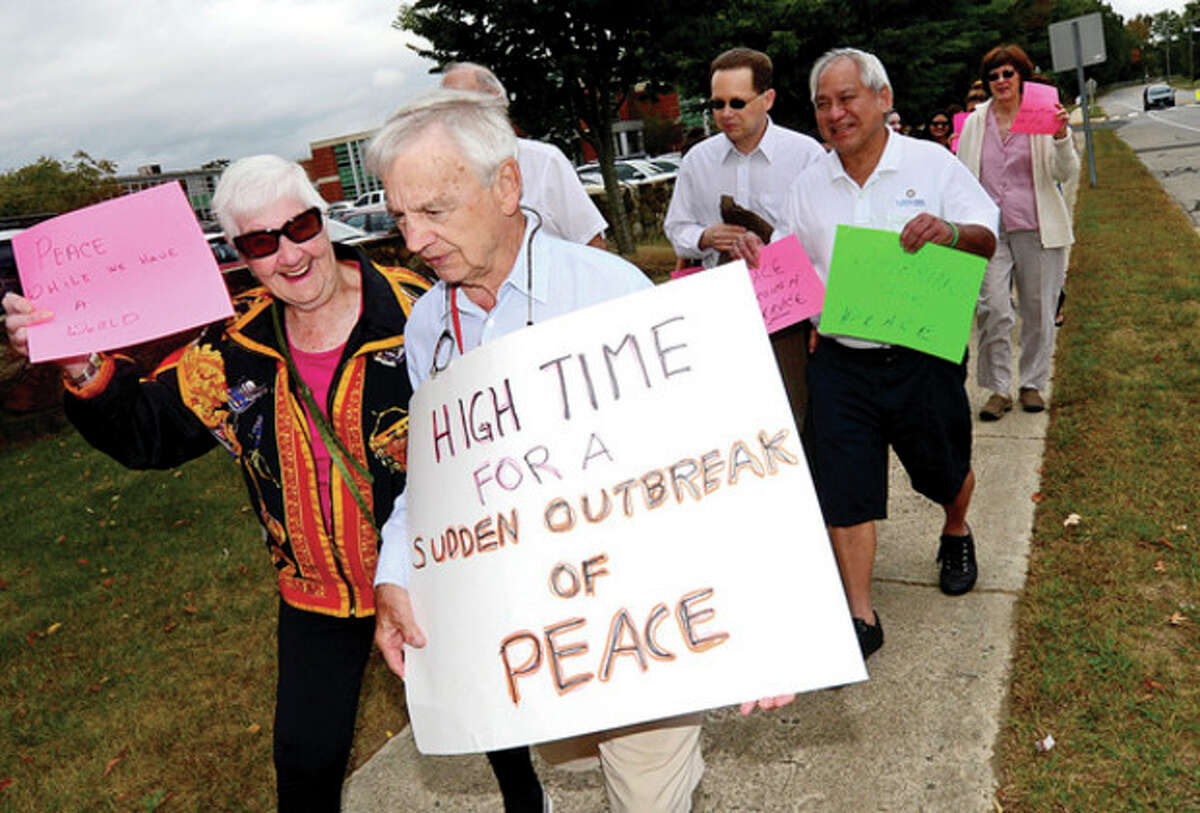 Hour photos / Erik Trautmann Above, Scott Kimmich and Mabel Dudeny participate in an outdoor Peace March from the front of the East Campus at Norwalk Community College building to the Post Road and back Saturday. Above right, Alex LaBonte holds a sign pledging to be nice.