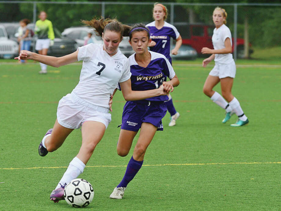 Hour photo/Erik TrautmannWilton's Haley English, left, battles against a Westhill defender during Saturday's game at Wilton's Lilly Field. The visiting Vikings made off with a 1-0 victory. / ©2012 Pascal Photographic Studios