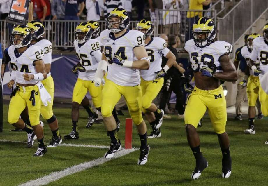 Michigan players run onto the field before an NCAA college football game against Connecticut, Saturday, Sept. 21, 2013, in East Hartford, Conn. (AP Photo/Charles Krupa)