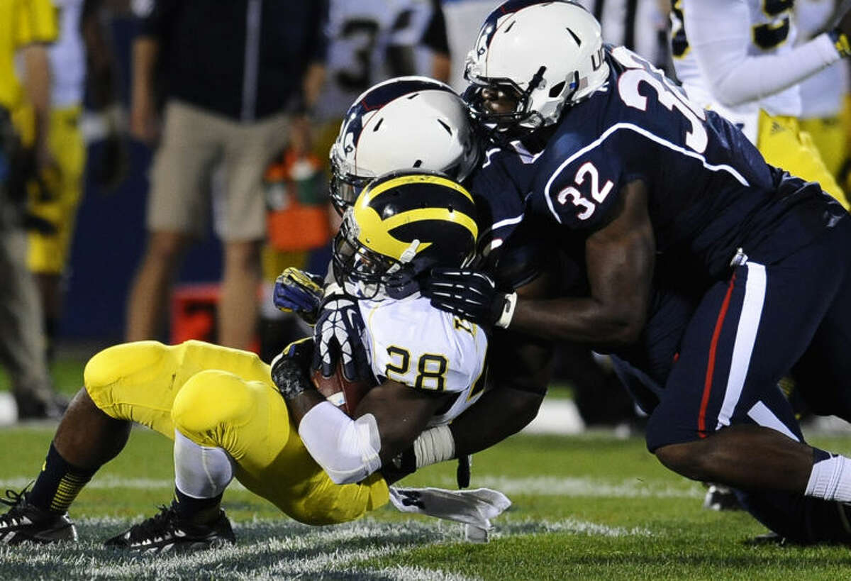 Connecticut linebacker Jefferson Ashiru (32), right, and Connecticut defensive tackle Angelo Pruitt (56), center, stop Michigan running back Fitzgerald Toussaint (28) during the first half of an NCAA college football game at Rentschler Field, Saturday, Sept. 21, 2013, in East Hartford, Conn., Saturday. (AP Photo/Jessica Hill)