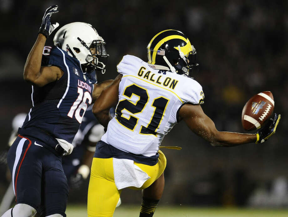Connecticut cornerback Byron Jones (16) is called for pass interference as Michigan wide receiver Jeremy Gallon (21) reaches for the ball during the first half of an NCAA college football game at Rentschler Field, Sept. 21, 2013, in East Hartford, Conn., Saturday. (AP Photo/Jessica Hill)