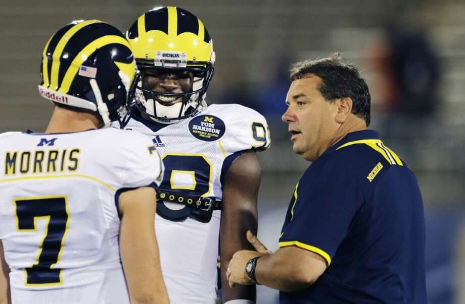 Michigan head coach Brady Hoke, right, talks with quarterbacks Devin Gardner, center, and Shane Morris (7) before an NCAA college football game against Connecticut, Saturday, Sept. 21, 2013, in East Hartford, Conn. (AP Photo/Charles Krupa)