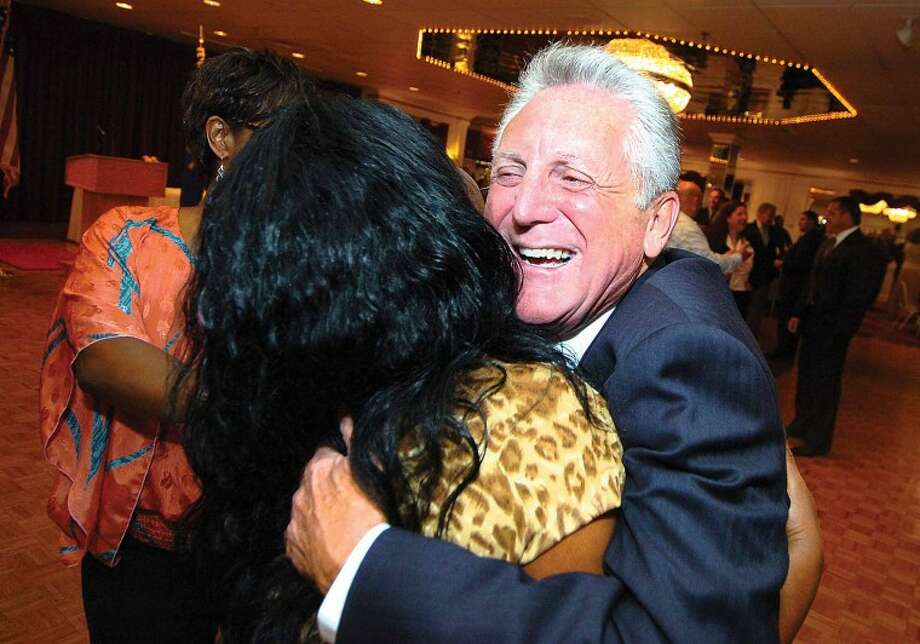 Hour Photo/ Alex von Kleydorff. Harry Rilling gets a big hug from Sally Johnson, Executive assistant for Mayor Moccia during his retirement party at Continental Manor on Thursday night.