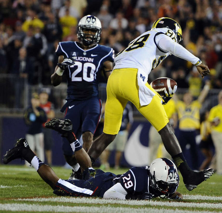 Michigan quarterback Devin Gardner (98), top, runs over Connecticut cornerback Taylor Mack (29), bottom, to score a touchdown during the first half of an NCAA college football game at Rentschler Field, Saturday, Sept. 21, 2013, in East Hartford, Conn., Saturday. (AP Photo/Jessica Hill)