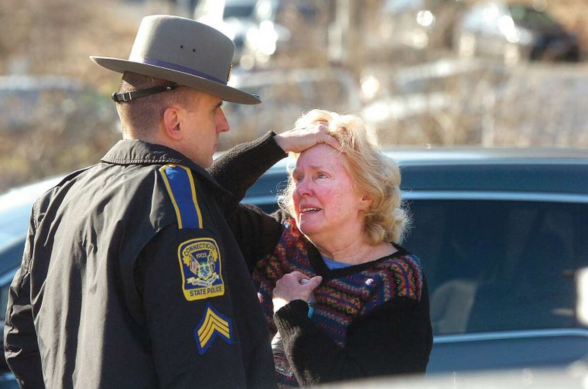 Hour Photo/Alex von Kleydorff. People are comforted near the scene of a mass shooting at Sandy Hook School in Newtown Ct on Friday morning.
