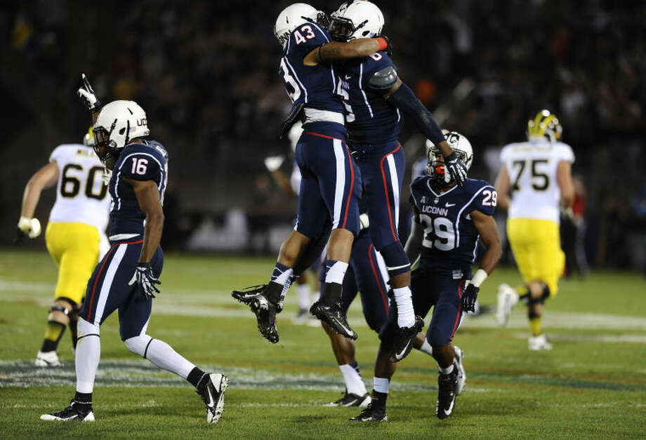Connecticut cornerback Byron Jones (16), and running back Lyle McCombs (43), and cornerback Taylor Mack (29), right, celebrate with cornerback Jhavon Williams (6) who intercepted the ball during the first half of an NCAA college football game against Michigan at Rentschler Field, Saturday, Sept. 21, 2013, in East Hartford, Conn., Saturday. (AP Photo/Jessica Hill)