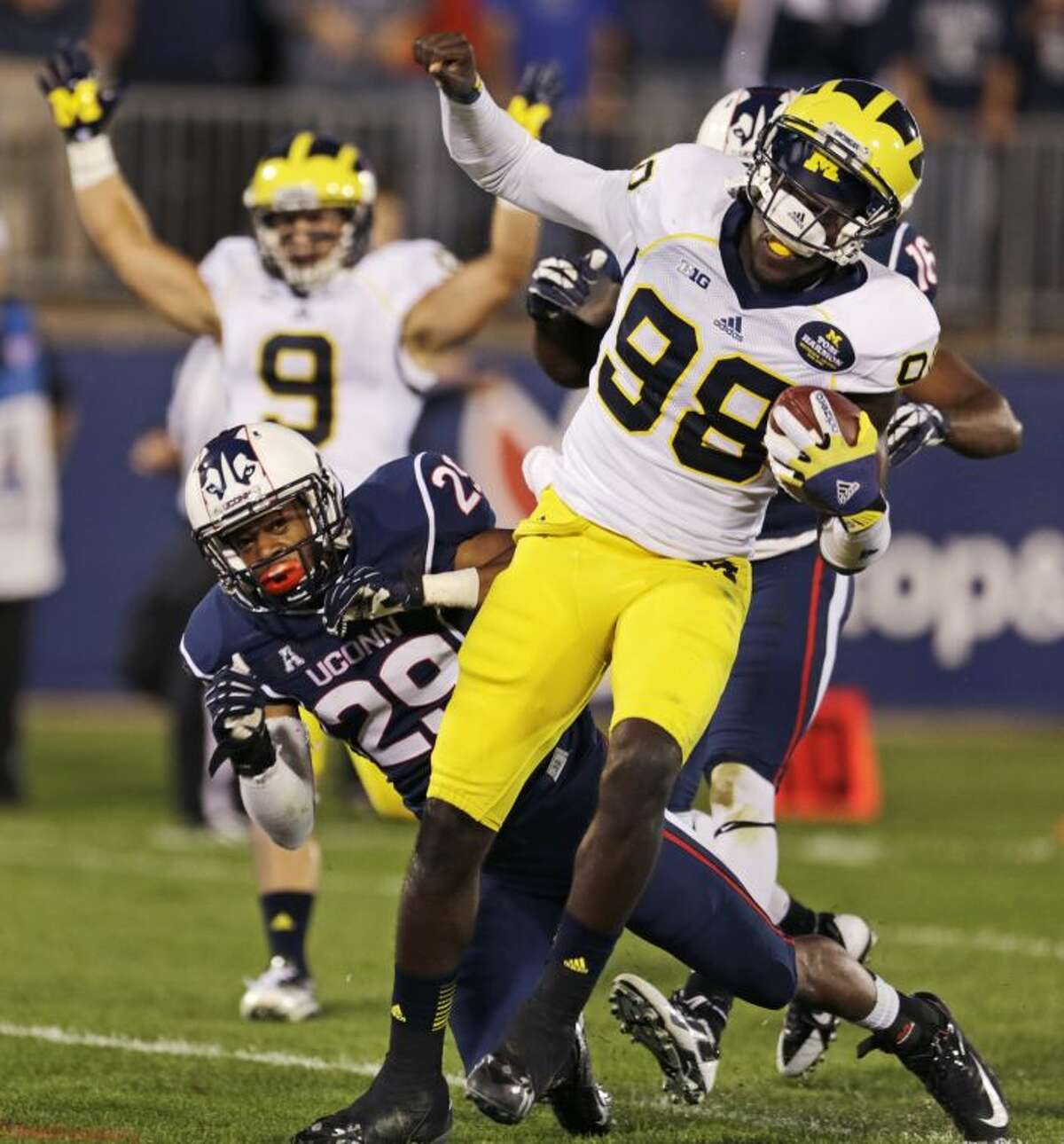 Michigan quarterback Devin Gardner (98) crosses the goal line, passing Connecticut cornerback Taylor Mack (29), for a touchdown during the first quarter of an NCAA college football game on Saturday, Sept. 21, 2013, in East Hartford, Conn. (AP Photo/Charles Krupa)