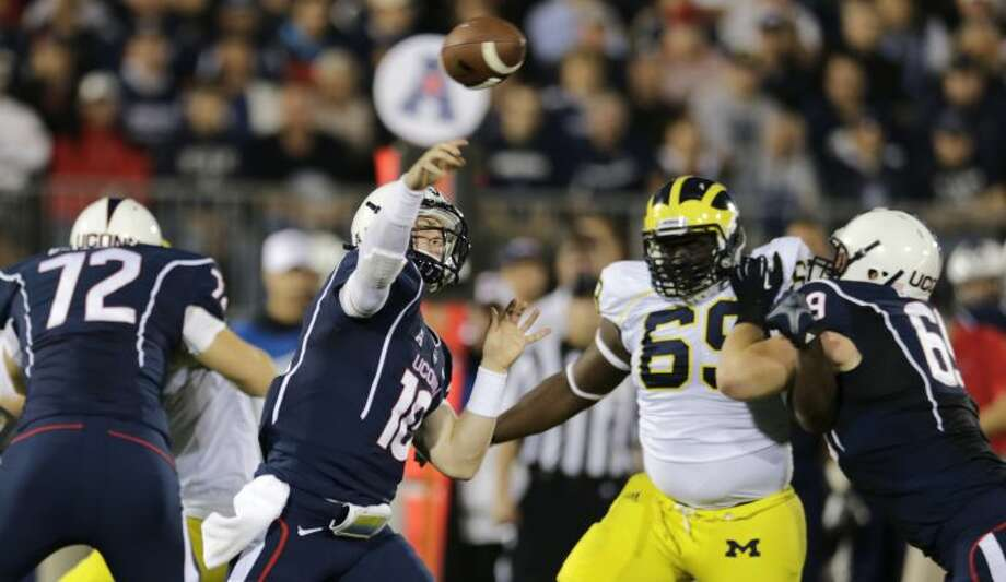 Connecticut quarterback Chandler Whitmer (10) throws as he is pressured by Michigan defensive tackle Willie Henry (69) during the first quarter of an NCAA college football game on Saturday, Sept. 21, 2013, in East Hartford, Conn. (AP Photo/Charles Krupa)