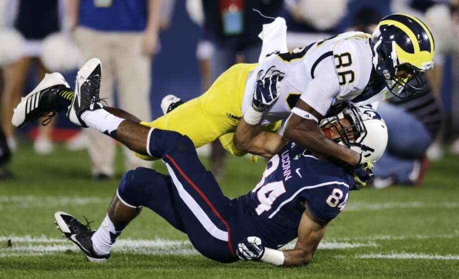 Michigan's Jehu Chesson (86) levels Connecticut's Brian Lemelle (84) on a punt reception during the second quarter of an NCAA college football game on Saturday, Sept. 21, 2013, in East Hartford, Conn. (AP Photo/Charles Krupa)