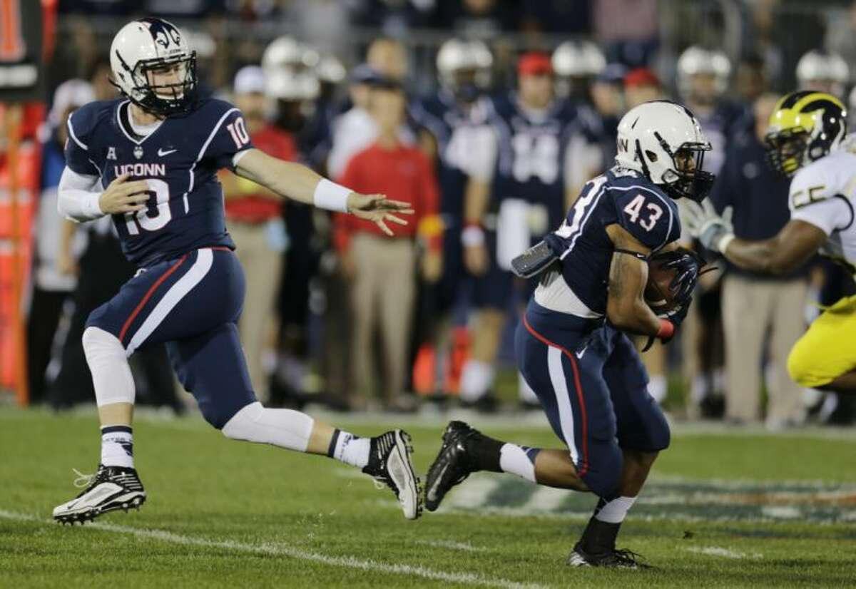 Connecticut quarterback Chandler Whitmer hands off to running back Lyle McCombs (43) during the first quarter of an NCAA college football game against Michigan, Saturday, Sept. 21, 2013, in East Hartford, Conn. (AP Photo/Charles Krupa)