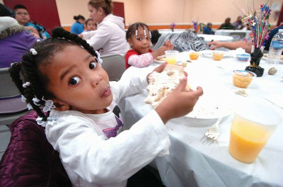 Hour Photo Alex von Kleydorff; 4yr old Enya Etienne has a bagel with cream cheese for breakfast with her family at NEON on Friday morning. Meals were prepared and served with help from GE Capitol volunteers that included pancakes, waffles, bacon, muffins and coffee and juice.