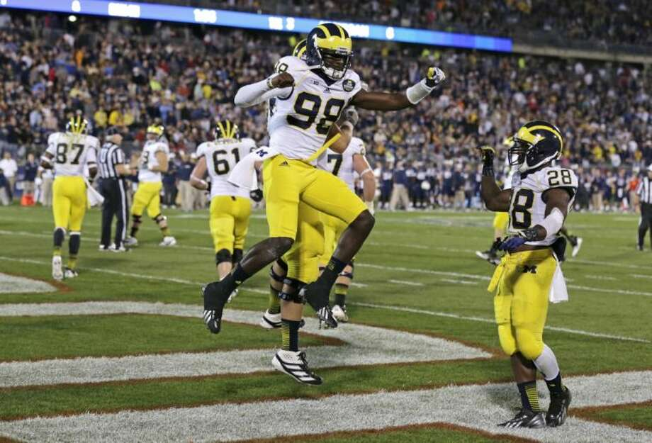 Michigan quarterback Devin Gardner celebrates after scoring a touchdown during the first quarter of an NCAA college football game against Connecticut, Saturday, Sept. 21, 2013, in East Hartford, Conn. (AP Photo/Charles Krupa)