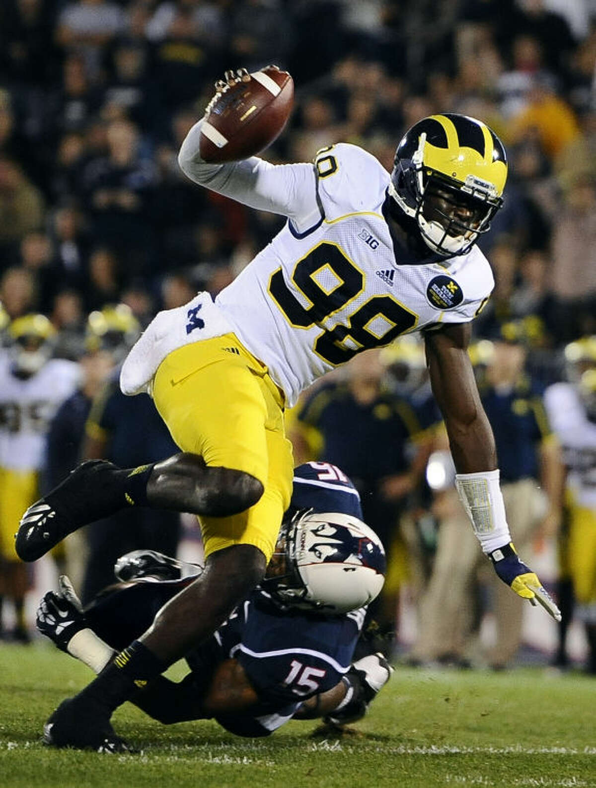 Michigan quarterback Devin Gardner (98), top, breaks past Connecticut safety Ty-Meer Brown (15) for a touchdown during the first half of an NCAA college football game at Rentschler Field, Saturday, Sept. 21, 2013, in East Hartford, Conn. (AP Photo/Jessica Hill)