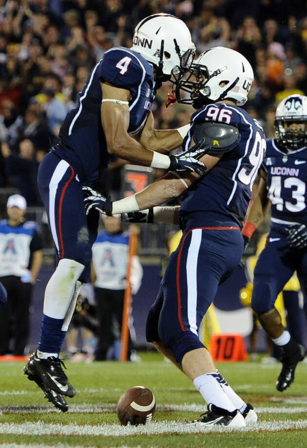 Connecticut wide receiver Deshon Foxx (4) celebrates with teammate Spencer Parker (96) after Parker's touchdown during the first half of an NCAA college football game against Michigan at Rentschler Field, Saturday, Sept. 21, 2013, in East Hartford, Conn. (AP Photo/Jessica Hill)
