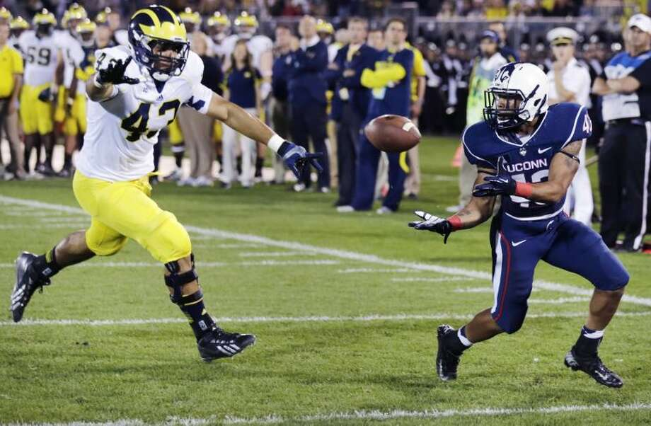 Connecticut running back Lyle McCombs, right, hauls in a touchdown pass against Michigan defensive lineman Chris Wormley, left, during the second quarter of an NCAA college football game on Saturday, Sept. 21, 2013, in East Hartford, Conn. (AP Photo/Charles Krupa)