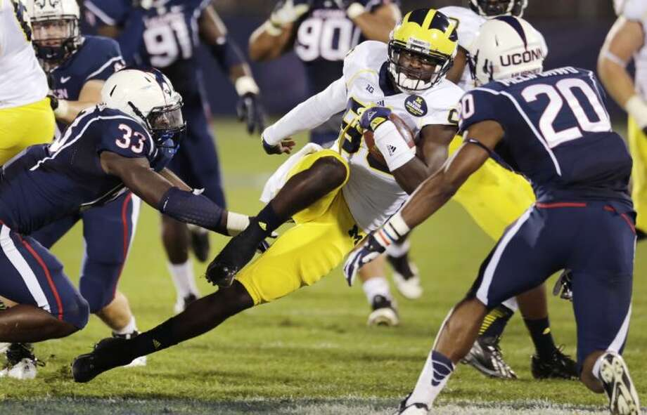 Michigan quarterback Devin Gardner, center, tries to elude Connecticut linebacker Yawin Smallwood (33) and safety Obi Melifonwu (20) during the first quarter of an NCAA college football game on Saturday, Sept. 21, 2013, in East Hartford, Conn. (AP Photo/Charles Krupa)