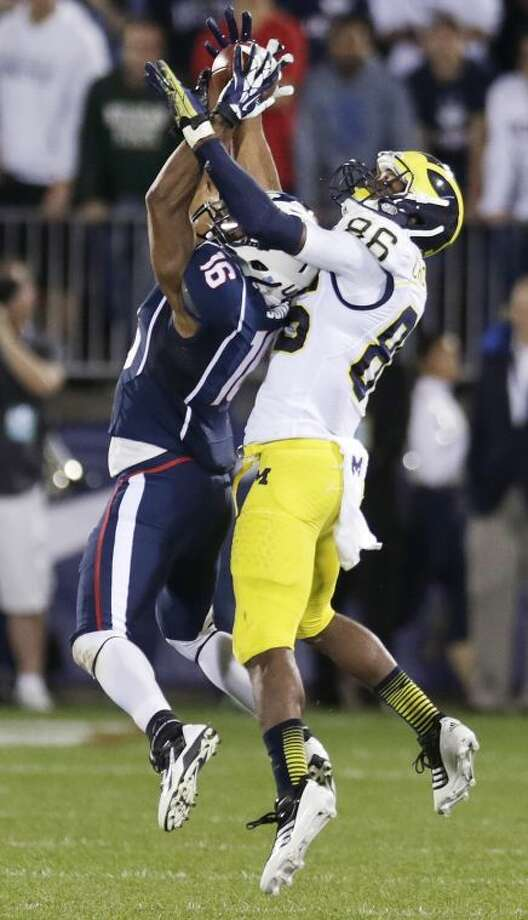 Connecticut cornerback Byron Jones (16) intercepts a pass intended for Michigan wide receiver Jehu Chesson (86) during the second quarter of an NCAA college football game on Saturday, Sept. 21, 2013, in East Hartford, Conn. (AP Photo/Charles Krupa)