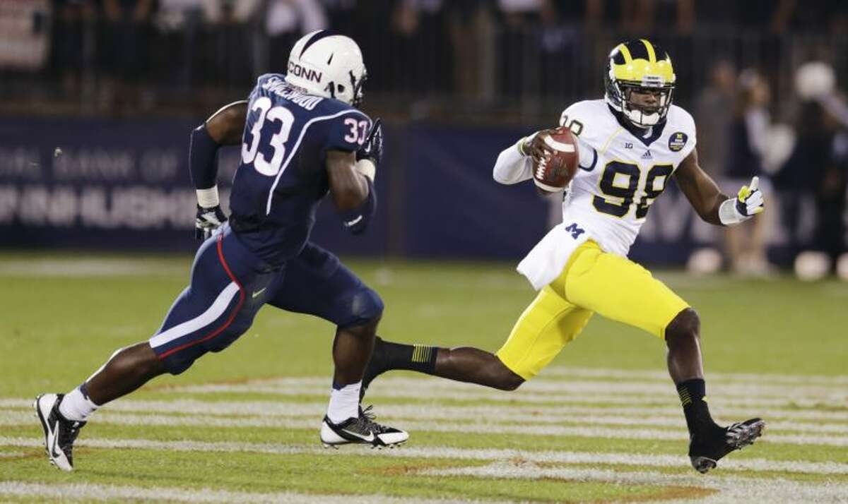 Michigan quarterback Devin Gardner (98) scrambles away from Connecticut linebacker Yawin Smallwood (33) during the first quarter of an NCAA college football game on Saturday, Sept. 21, 2013, in East Hartford, Conn. (AP Photo/Charles Krupa)