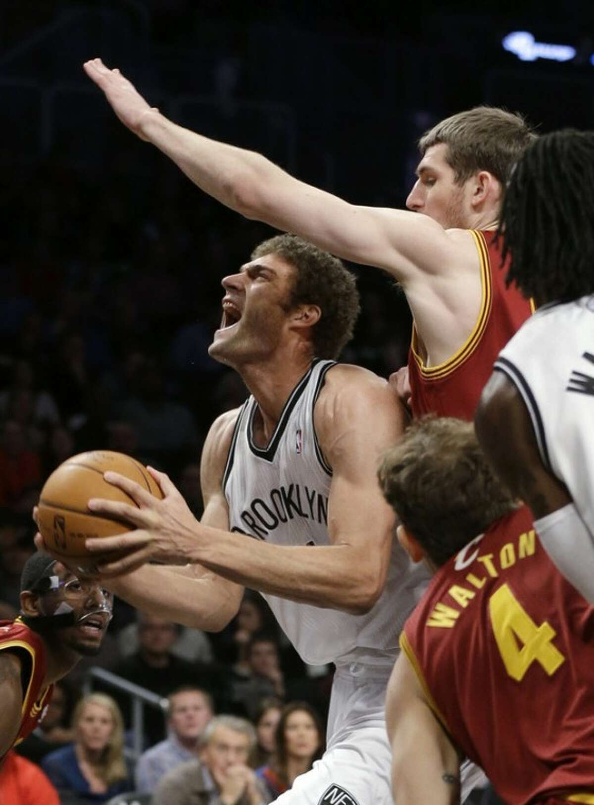Brooklyn Nets' Brook Lopez drives past Cleveland Cavaliers' Tyler Zeller, top right, during the first half of an NBA basketball game Saturday, Dec. 29, 2012, in New York. (AP Photo/Frank Franklin II)