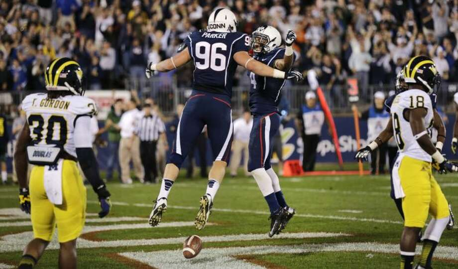 Connecticut tight end Spencer Parker (96) celebrates his touchdown with wide receiver Deshon Foxx namduring the second quarter of an NCAA college football game against Michigan, Saturday, Sept. 21, 2013, in East Hartford, Conn. (AP Photo/Charles Krupa)