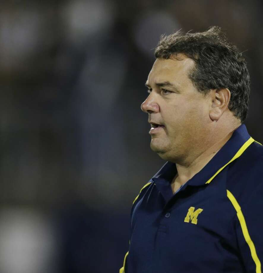Michigan head coach Brady Hoke walks onto the field before an NCAA college football game against Connecticut, Saturday, Sept. 21, 2013, in East Hartford, Conn. (AP Photo/Charles Krupa)