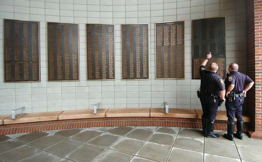 Hour Photo Alex von Kleydorff; Two Norwalk Motorcycle Police stop and look at names of Norwalk's Veterans on the plaques at the entrance to City Hall
