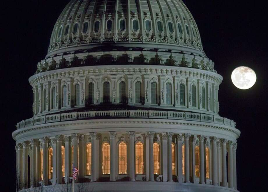 "The moon rises behind the U.S. Capitol Dome in Washington as Congress works into the late evening, Sunday, Dec. 30, 2012 to resolve the stalemate over the pending ""fiscal cliff."" (AP Photo/J. David Ake) / AP"