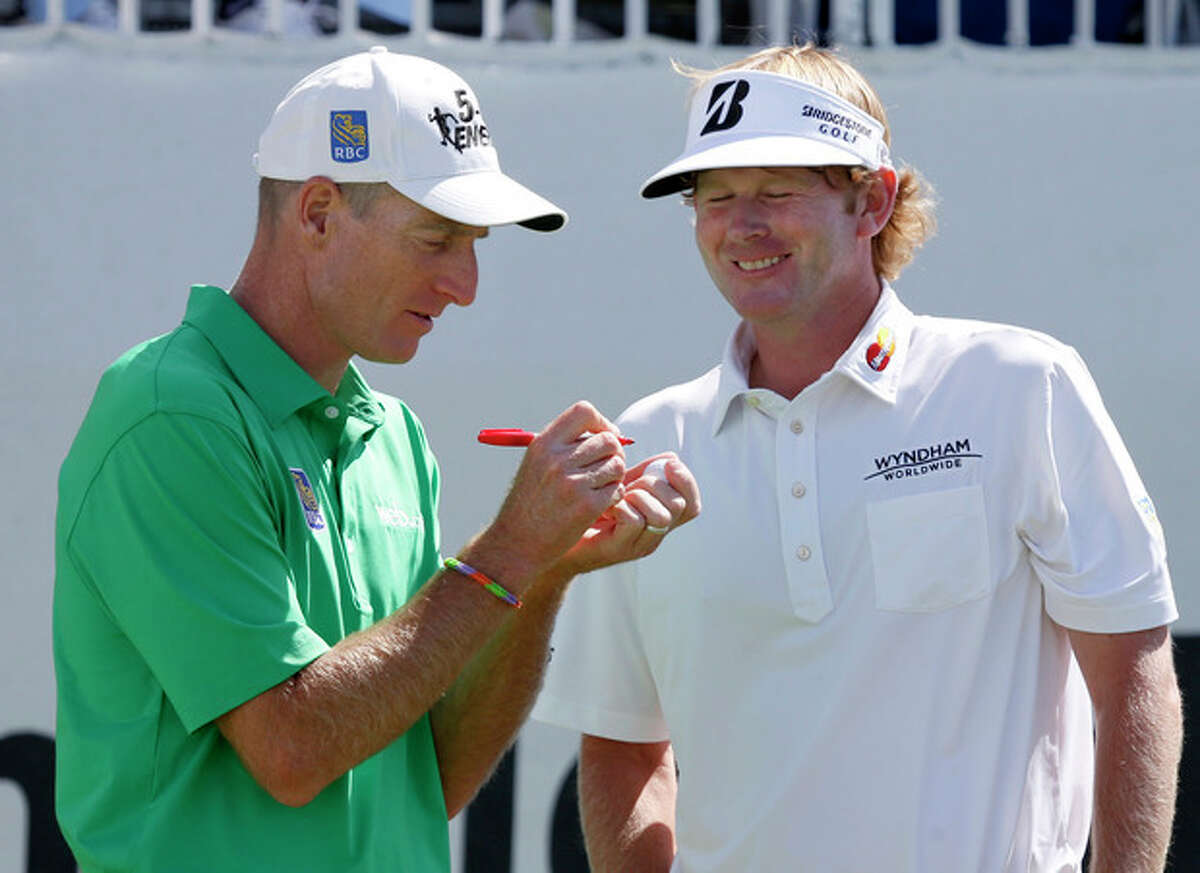 Brandt Snedeker, right, smiles as Jim Furyk marks his ball during the third round of the BMW Championship golf tournament at Conway Farms Golf Club in Lake Forest, Ill., Saturday, Sept. 14, 2013. (AP Photo/Charles Rex Arbogast)