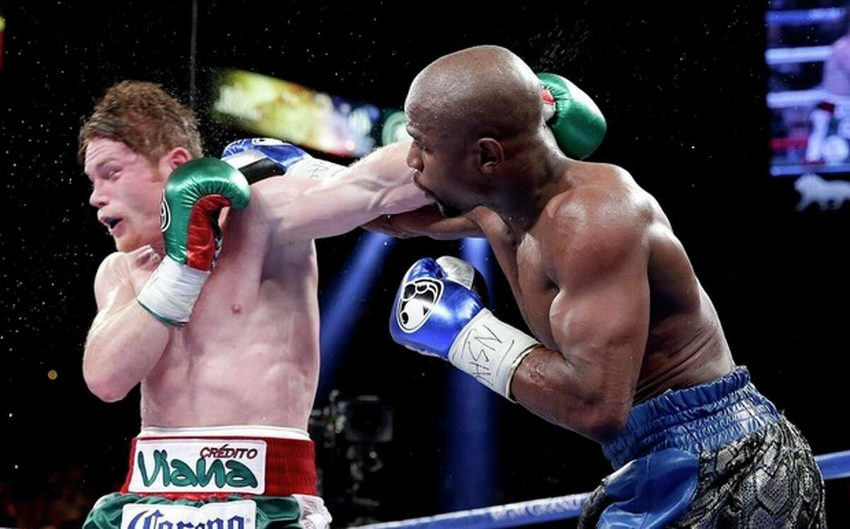 Floyd Mayweather Jr. lands a punch against Canelo Alvarez in the ninth round during a 152-pound title fight, Saturday, Sept. 14, 2013, in Las Vegas. (AP Photo/Eric Jamison)