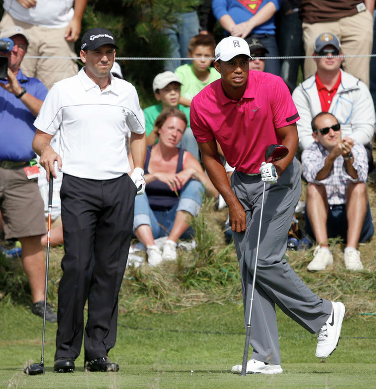 Sergio Garcia, left, and Tiger Woods watch Wood's tee shot on the 14th hole during the third round of the BMW Championship golf tournament at Conway Farms Golf Club in Lake Forest, Ill., Saturday, Sept. 14, 2013. (AP Photo/Charles Rex Arbogast)