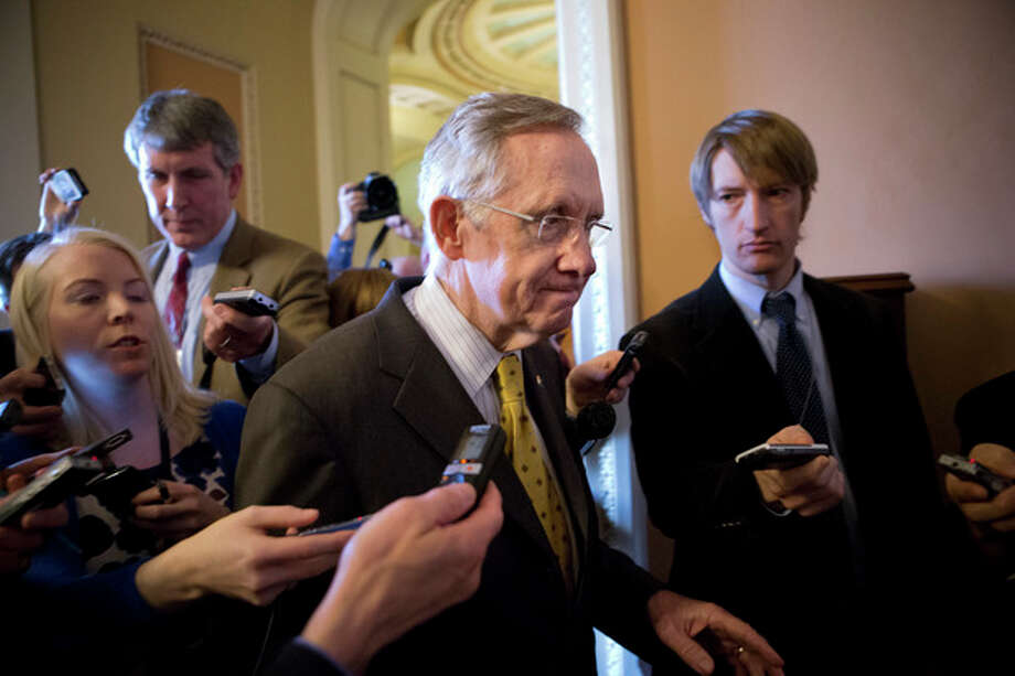 "Senate Majority Leader Harry Reid, D-Nev., walks to a closed-door meeting with fellow Democrats as he and Senate Minority Leader Mitch McConnell, R-Ky., work to negotiate a legislative path to avoid the so-called ""fiscal cliff,"" at the Capitol in Washington, Sunday, Dec. 30, 2012. Senate and House leaders are rushing to assemble a last-ditch agreement to stave off middle-class tax increases and possibly delay steep spending cuts in an urgent attempt to find common ground after weeks of gridlock. (AP Photo/J. Scott Applewhite) / AP"