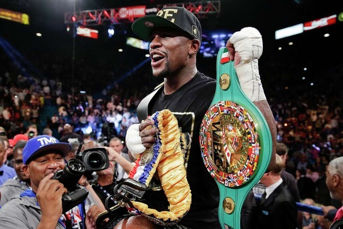Floyd Mayweather Jr. holds up his title belts after defeating Canelo Alvarez during a 152-pound title fight, Saturday, Sept. 14, 2013, in Las Vegas. (AP Photo/Eric Jamison)