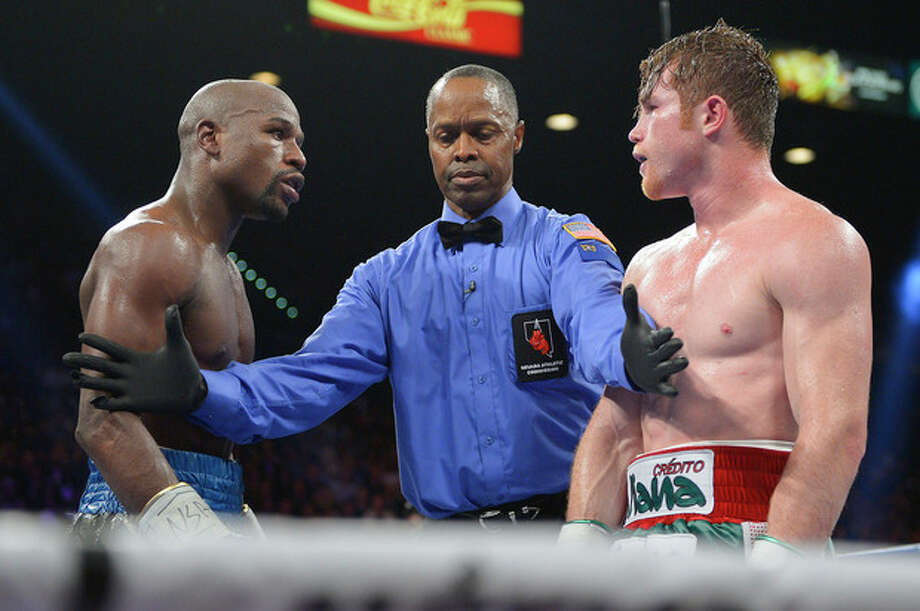 Referee Kenny Bayless, center, separates Floyd Mayweather Jr., left, and Canelo Alvarez at the end of the 11th round during a 152-pound title fight, Saturday, Sept. 14, 2013, in Las Vegas. (AP Photo/Mark J. Terrill) / AP
