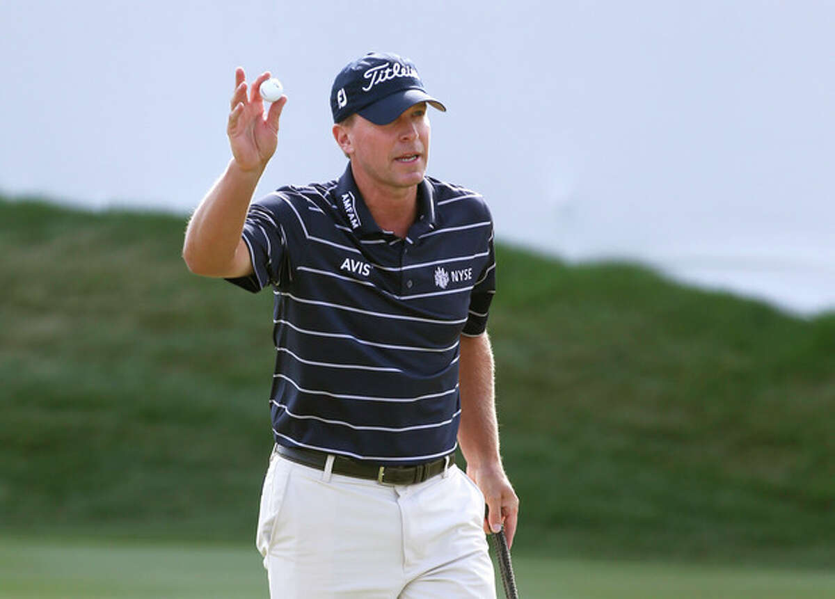 Steve Stricker acknowledges the gallery after making birdie on the 18th green during the third round of the BMW Championship golf tournament at Conway Farms Golf Club in Lake Forest, Ill., Saturday, Sept. 14, 2013. (AP Photo/Charles Rex Arbogast)