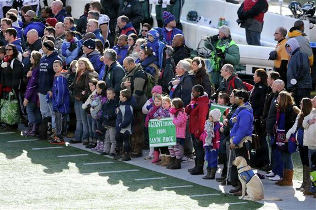 A contingent of teachers, parents, and students from Sandy Hook Elementary School in Newtown, Conn., take part in ceremonies before Sunday's game between the New York Giants and the Philadelphia Eagles at MetLife Stadium, Sunday, Dec. 30, 2012, in East Rutherford, N.J. The school was the site of a mass shooting on Dec. 14. (AP Photo/Peter Morgan)