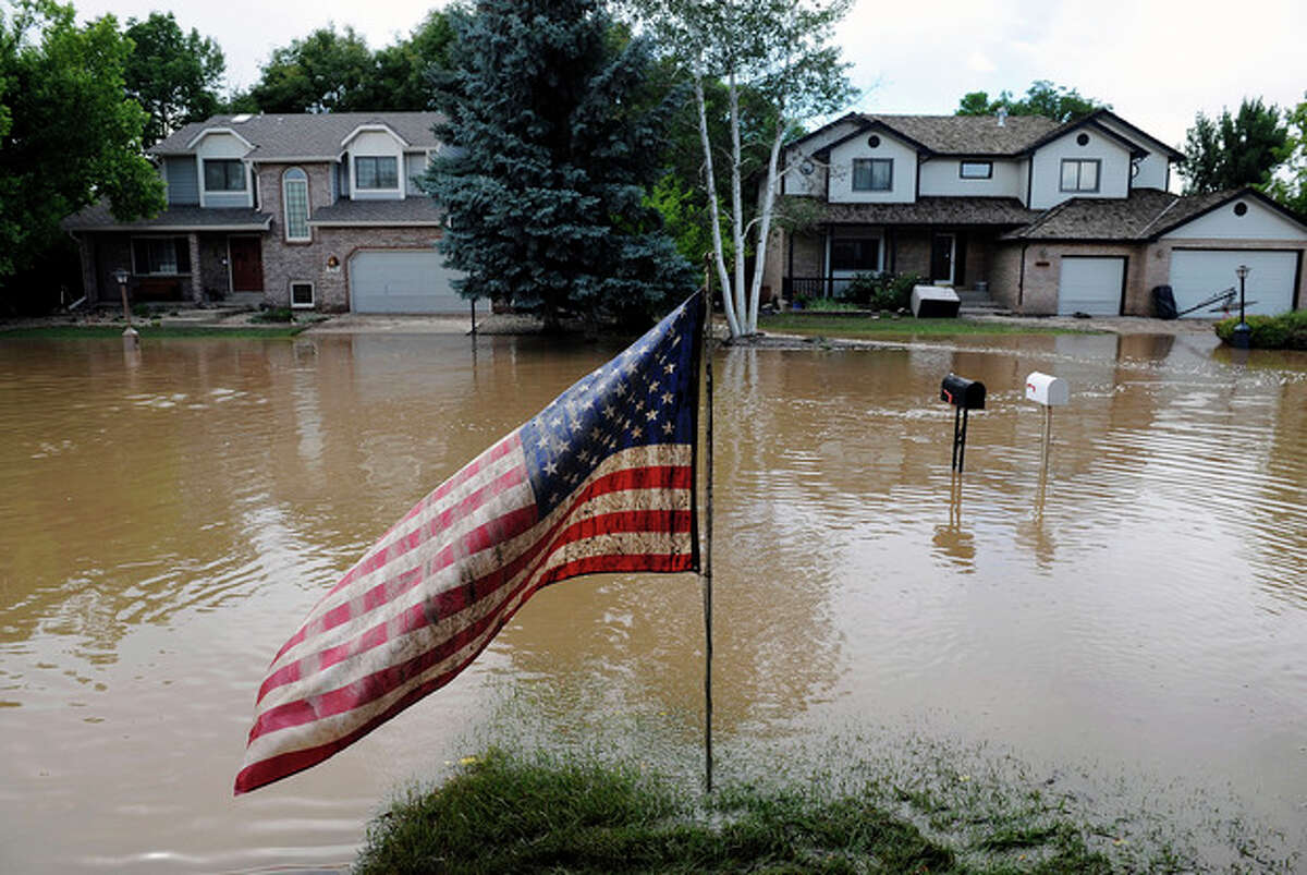 A muddy U.S. flag stands in front of flooded homes in Longmont, Colo., on Saturday, Sept. 14, 2013. Floodwaters have affected a 4,500 square-mile section of the state. National Guard helicopters have been evacuating residents from the hardest hit communities. (AP Photo/Chris Schneider)
