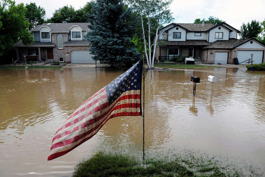 A muddy U.S. flag stands in front of flooded homes in Longmont, Colo., on Saturday, Sept. 14, 2013. Floodwaters have affected a 4,500 square-mile section of the state. National Guard helicopters have been evacuating residents from the hardest hit communities. (AP Photo/Chris Schneider) / FR170036 AP
