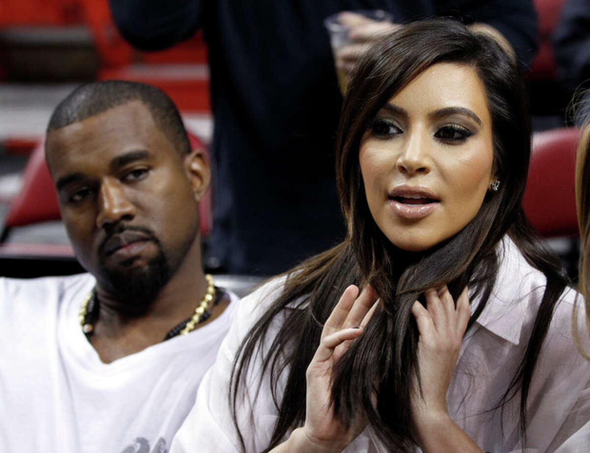 FILE - Kim Kardashian, right, and Kanye West, left, are shown before an NBA basketball game between the Miami Heat and the New York Knicks in this Dec, 6, 2012 file photo taken in Miami. The rapper Kanye West announced at a concert Sunday night Dec. 30, 2012 that his girlfriend is pregnant. He told the crowd of more than 5,000 at the Ovation Hall at the Revel Resort in song form: