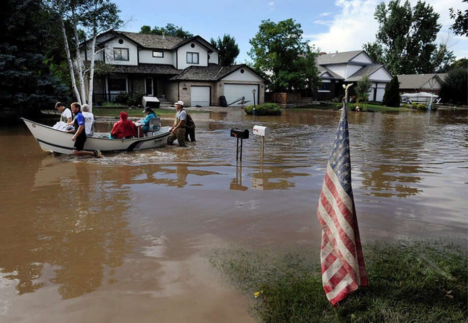 A boat carrying residents back to their homes to gather pets and belongings goes past a muddy U.S. flag in a residential neighborhood in Longmont, Colo., on Saturday, Sept. 14, 2013. Floodwaters have affected a 4,500 square-mile section of the state. National Guard helicopters have been evacuating residents from the hardest hit communities. (AP Photo/Chris Schneider) / FR170036 AP