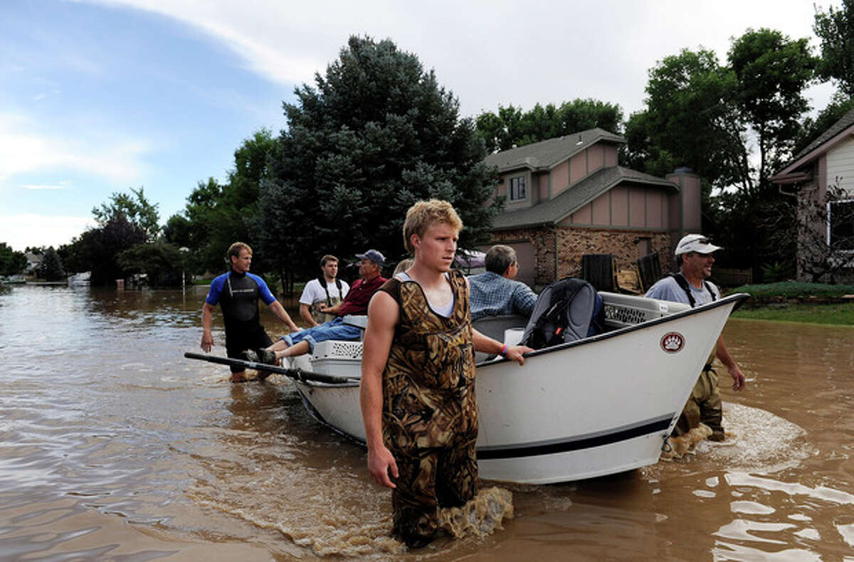 Brian Winn, rear left, Mitch Machmuller, rear center, Eric Machmuller, front center, and Pat Machmuller, right, steer a boat down a residential street to help residents gather pets and belongings from their flooded homes in Longmont, Colo., on Saturday, Sept. 14, 2013. Floodwaters have affected a 4,500 square-mile section of the state. National Guard helicopters have been evacuating residents from the hardest hit communities. (AP Photo/Chris Schneider)