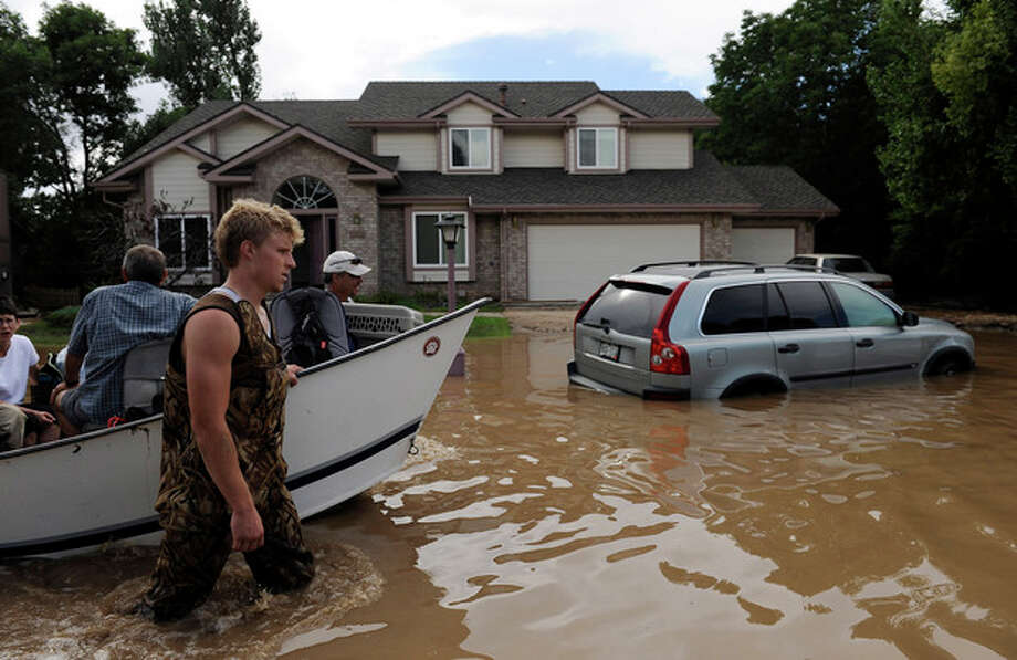 Ap photoEric Machmuller, front left, and Pat Machmuller, rear left, lead a boat down a residential street to help residents gather pets and belongings from their flooded homes in Longmont, Colo., on Saturday. / FR170036 AP