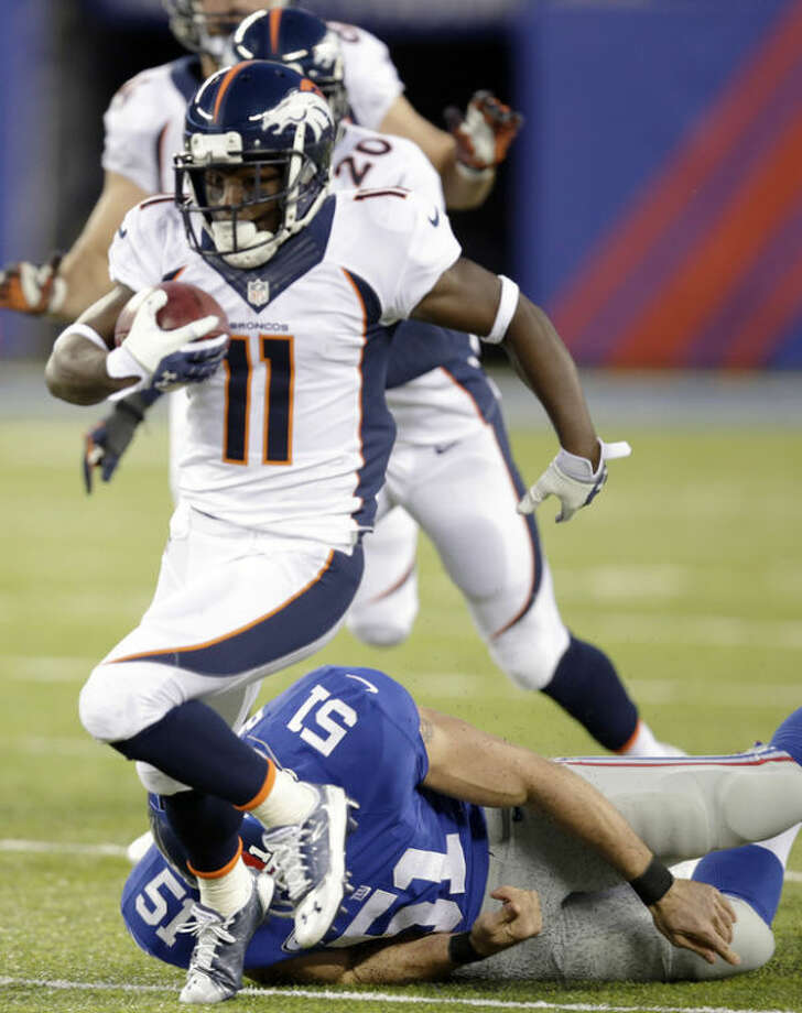 Denver Broncos wide receiver Trindon Holliday (11) runs away from New York Giants' Zak DeOssie (51) as he returns a punt for a touchdown during the second half of an NFL football game Sunday, Sept. 15, 2013, in East Rutherford, N.J. (AP Photo/Kathy Willens)