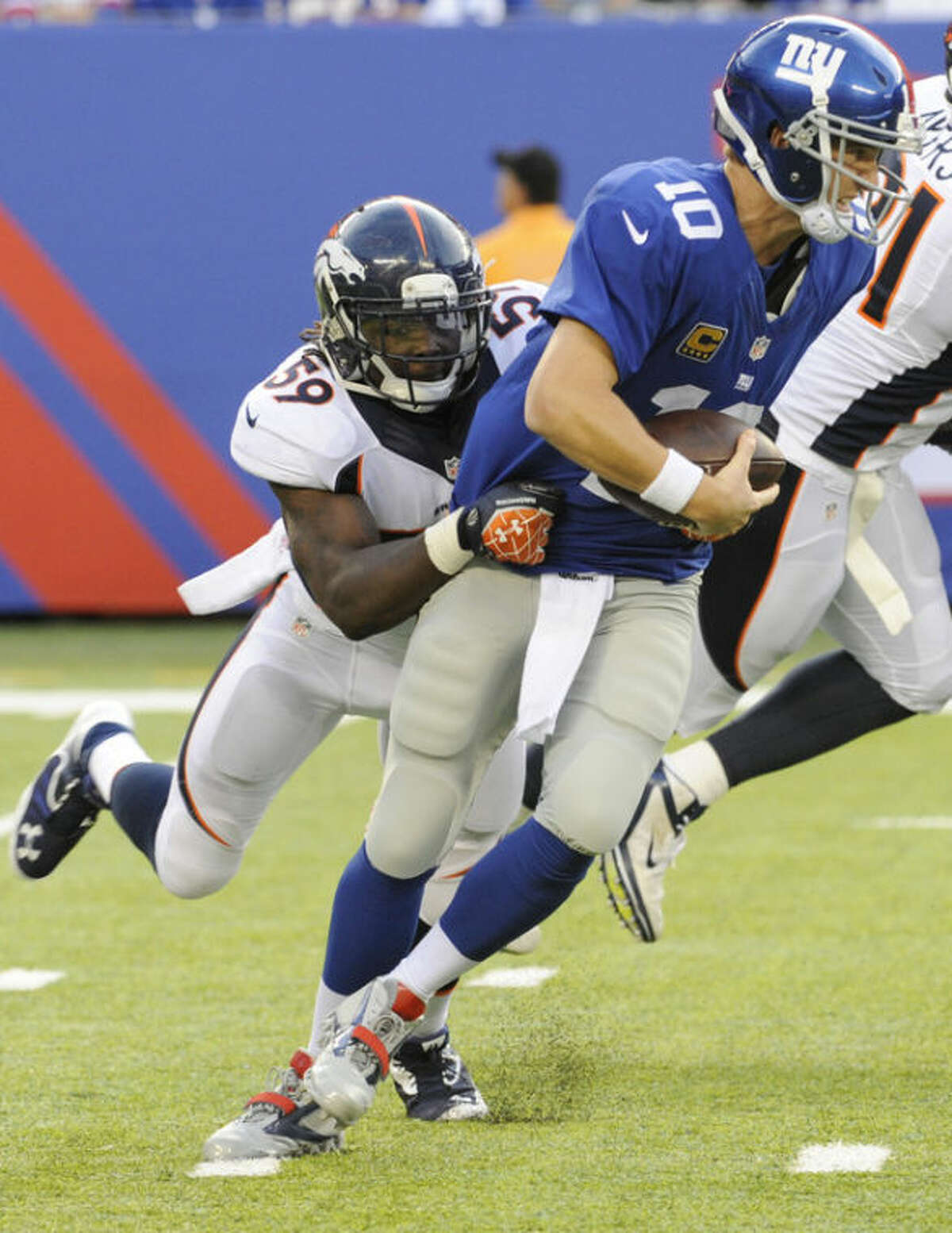 Denver Broncos' Danny Trevathan (59) sacks New York Giants quarterback Eli Manning (10) during the second half of an NFL football game Sunday, Sept. 15, 2013, in East Rutherford, N.J. (AP Photo/Bill Kostroun)